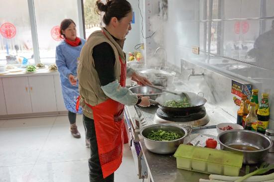 """01-社区""""老饭桌""""工作人员正在忙碌的炒菜.jpg"""
