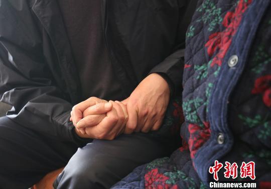 孙某紧紧握住母亲的手嘘寒问暖。 胡梦梅 摄