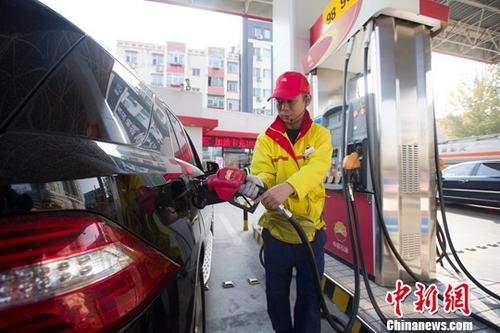 11月2日,山西太原一加油站内,工作人员正在给车辆加油。当日,中国国家发改委网站发布消息称,根据近期国际市场油价变化情况,按照现行成品油价格形成机制,自2018年11月2日24时起,中国国内汽、柴油价格(标准品,下同)每吨分别降低375元和365元人民币。中新社记者 张云 摄