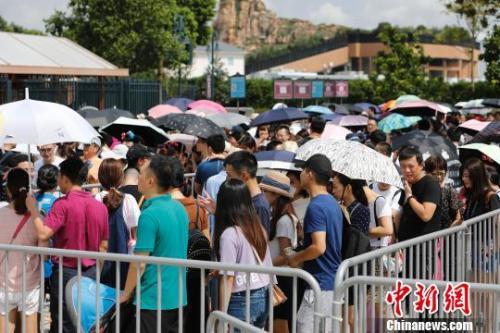 资料图:在迪士尼乐园门前,游客排队等待安检。 殷立勤 摄