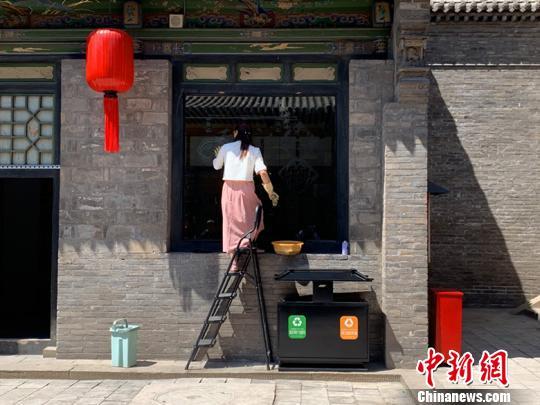 在景区内展示乔家大院文创产品的商铺里,工作人员正顶着太阳擦玻璃。 刘小红 摄