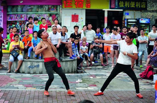"""2017年7月8日,在白石洲股份 公司附近,两名民间艺人在表 演""""钢筋绕脖""""绝艺。图/IC"""