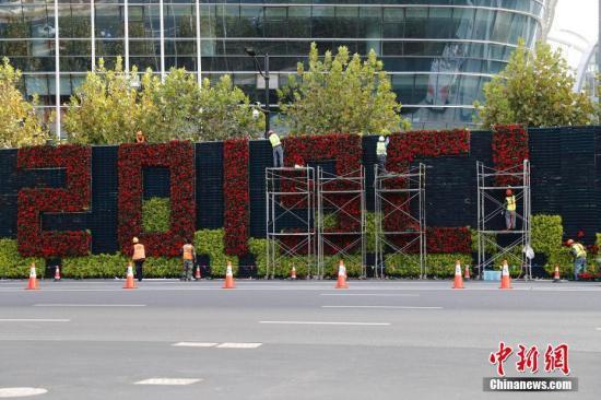 10月29日,国家会展中心(上海)南广场外,工作人员正在布置进博会主题景观。第二届中国国际进口博览会开幕在即,在进博会举办地——国家会展中心(上海),众多施工人员和展会志愿者正紧锣密鼓地进行展台搭建、标识完善、场馆清洁等布展工作。中新社记者 殷立勤 摄