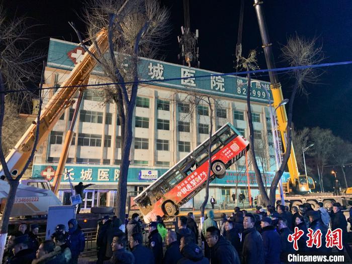 图为掉入坑内的公交车被起重机吊起 马铭言 摄