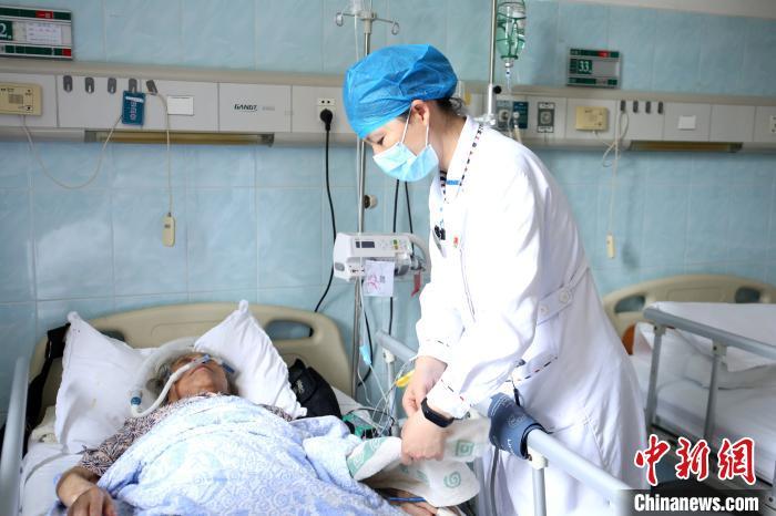 在柳州市工人医院,梁艳冰在帮病人整理被子。 朱柳融 摄