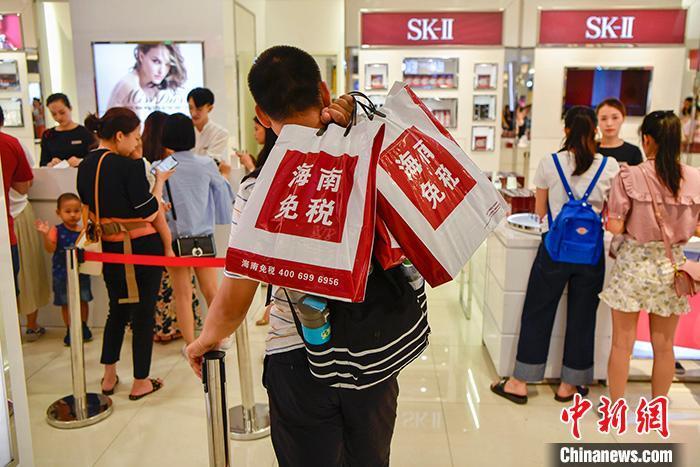 资料图为一位男顾客在海口日月广场免税店内排队买单。 中新社记者 骆云飞 摄