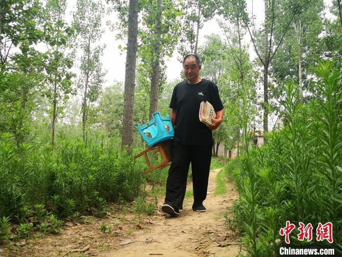 7月8日一早,柳玉春手拎小板凳前往日常自习的小树林复习功课。 阚力 摄