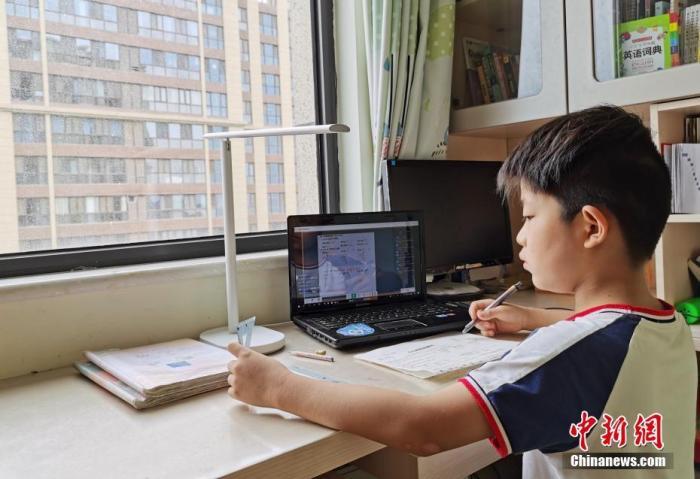 资料图:一小学生在家中通过平板电脑收看直播上数学课。 中新社记者 翟羽佳 摄