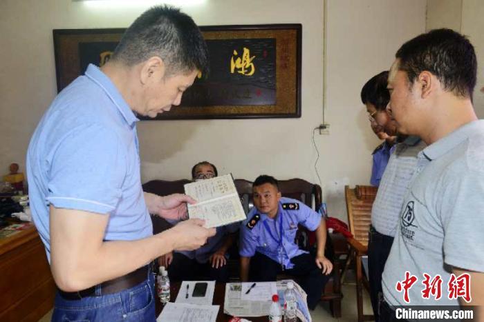 图为广西市场监管局工作人员查验经营户营业执照。广西市场监管局供图