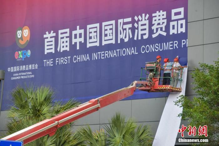 资料图:工作人员在海南国际会展中心外粘贴巨型主题宣传广告。中新社记者 骆云飞 摄